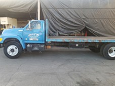 Used Ford Flat Bed Truck, model #F700 with 185,059 Miles. Used for hualing Machinery around Southern California. Has a bed weight capacity of 12,000 lbs. and the bed measures 8' x 20'